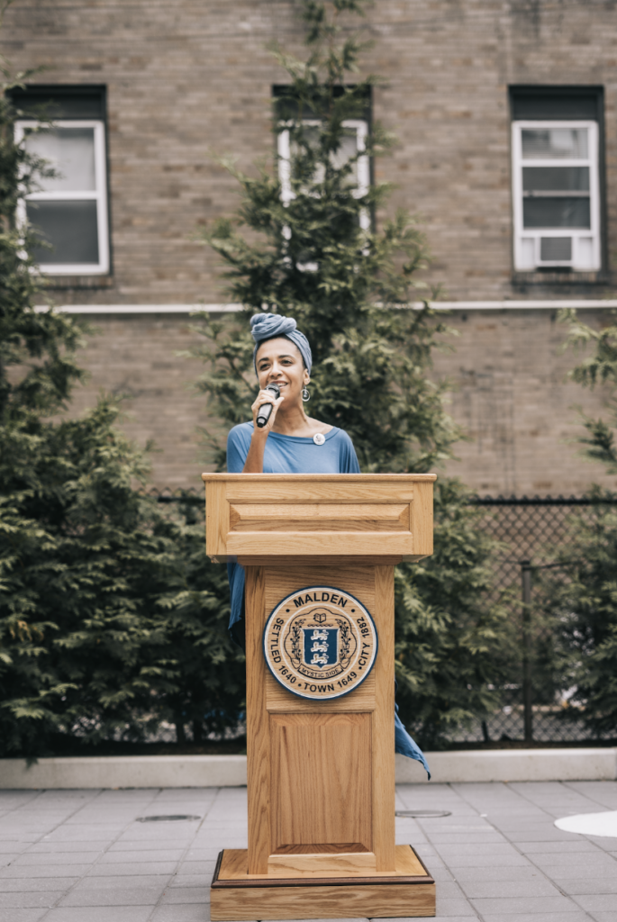 """Lydia """"LovelySinger"""" Harrell singing """"Lift Every Voice and Sing at the Juneteenth Flag Raising event. She is in front of a podium and there is a building and trees behind her."""